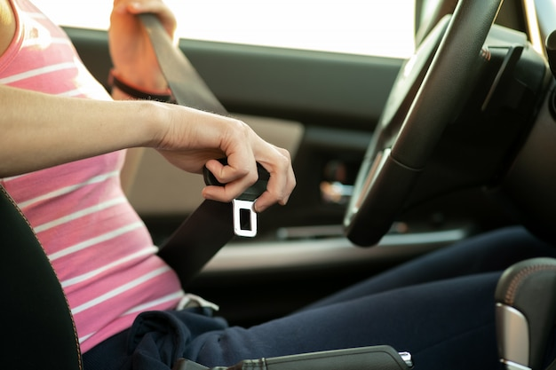 Schließen sie oben von frau hand, der sicherheitsgurt festhält, während sie in einem auto für sicherheit sitzen, bevor sie auf der straße fahren. fahrerin, die sicher fährt und sicher jorney nimmt.