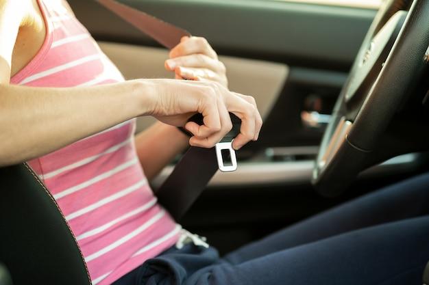 Schließen sie oben von frau hand, der sicherheitsgurt festhält, während sie in einem auto für sicherheit sitzen, bevor sie auf der straße fahren. fahrerin, die sicher fährt und sicheres jorney nimmt.