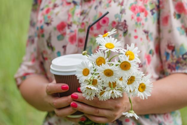 Schließen sie oben von frau mit kaffeetasse mit blumen im park
