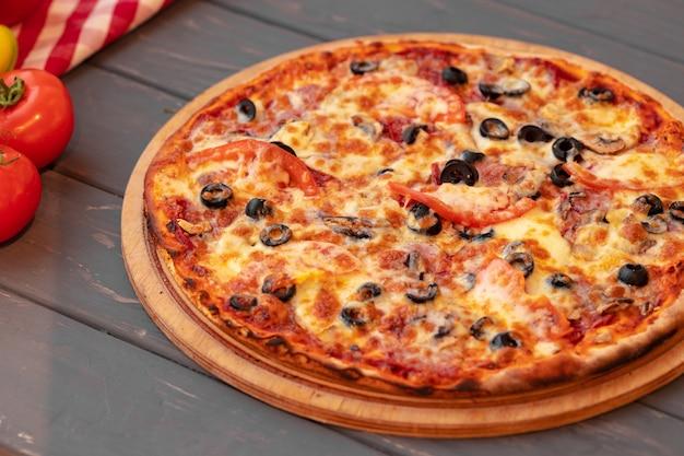 Schließen sie oben von frisch gebackener pizza auf schwarzem holztisch