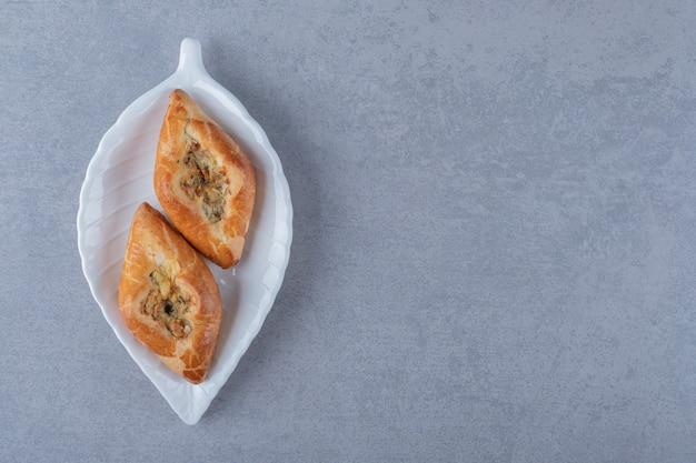 Schließen sie oben von frischen hausgemachten keksen auf weißem teller über grauer oberfläche