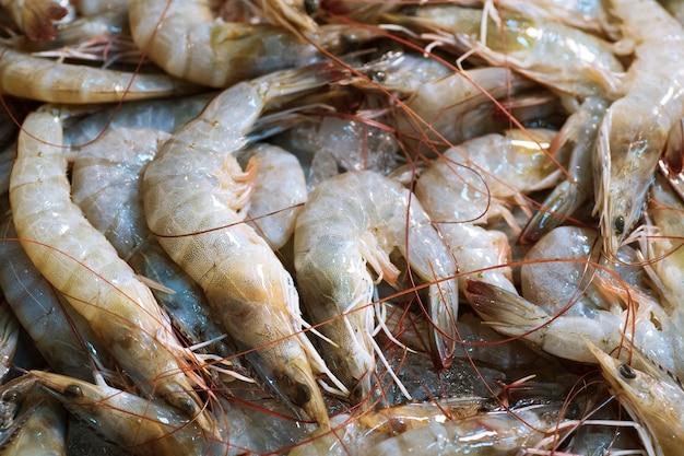 Schließen sie oben von frischen rohen garnelen gefroren auf dem eis, thailändischen straßenlebensmittelmarkt