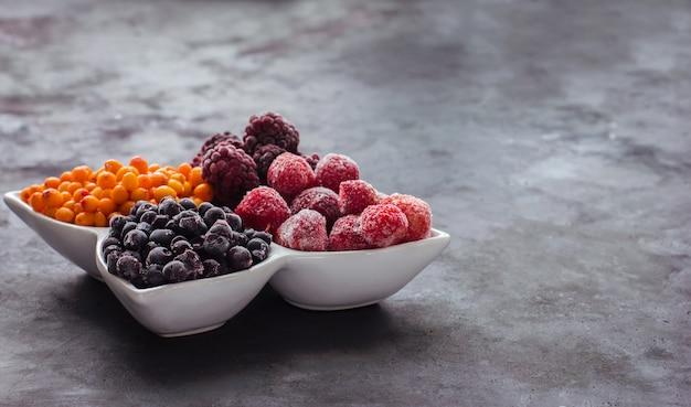 Schließen sie oben von gefrorenen gemischten früchten und beeren auf einem schwarzen tisch gesundes essen vitamine snack dessert
