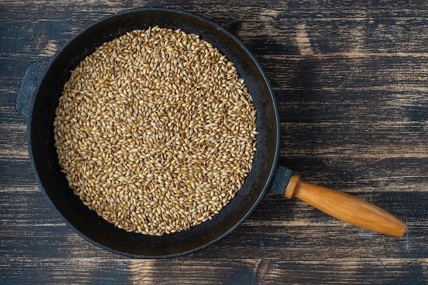 Schließen sie oben von gerösteten gerstenkörnern in einer gusseisernen pfanne auf tisch, draufsicht. zutat für bier oder kwas