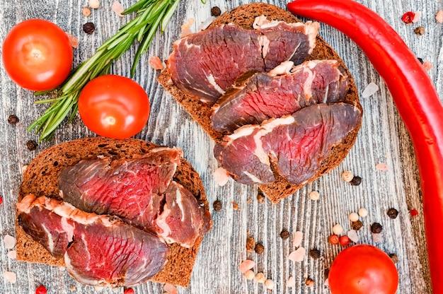 Schließen sie oben von geschnittenem trockenem fleisch auf dem holztisch