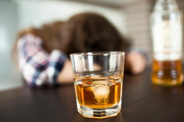 Schließen sie oben von glas und flasche mit whisky nach innen. betrunkene frau schläft.