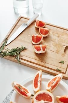 Schließen sie oben von grapefruitstücken messer und rosmarin auf holzschreibtisch. speicherplatz kopieren.