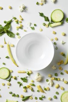 Schließen sie oben von grünem gemüse und obst auf dem teller für weißen tisch. gesunde ernährung und essen für veganer