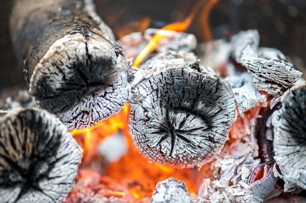 Schließen sie oben von hell brennenden holzstämmen mit gelben heißen feuerflammen