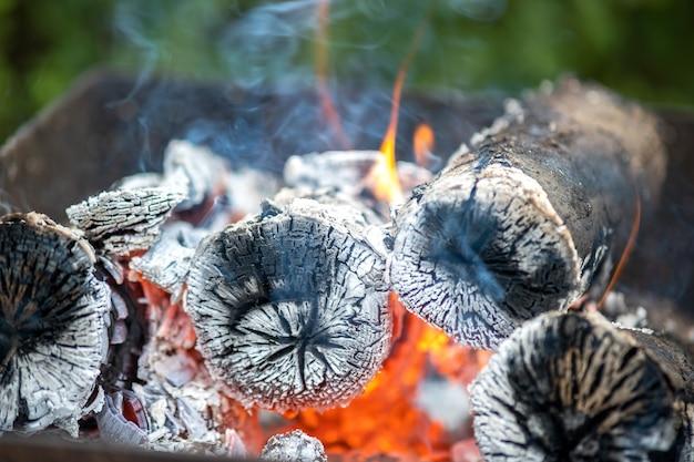 Schließen sie oben von hell brennenden holzstämmen mit gelben heißen feuerflammen.
