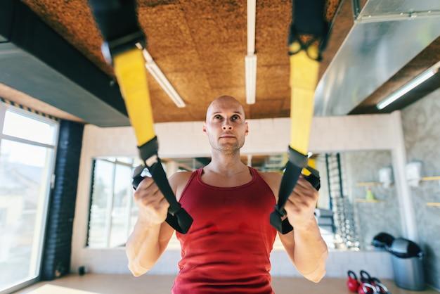 Schließen sie oben von kahlem sportlichem kaukasischem mann in der sportbekleidung, die trx-training beim stehen im fitnessstudio tut.