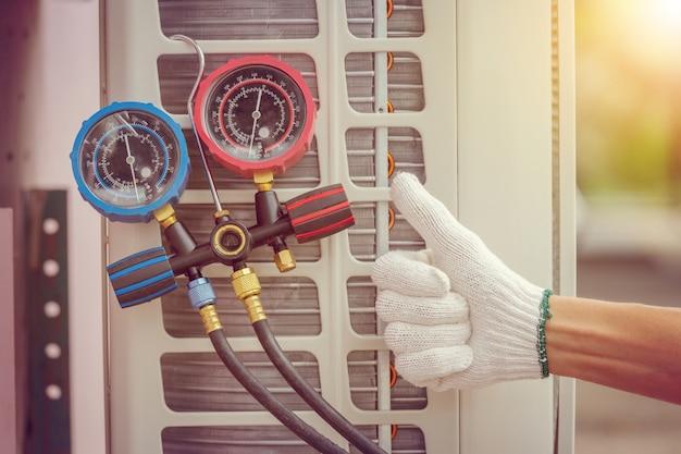 Schließen sie oben von klimaanlage-reparatur, schlosser auf dem boden, der klimaanlage repariert