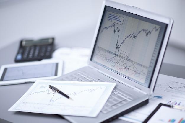 Schließen sie oben von laptop mit geschäftsdiagramm am arbeitsplatz. buchhaltungs- und berichtskonzept.