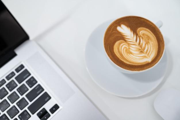 Schließen sie oben von latte art kaffeetasse mit tastatur des laptops