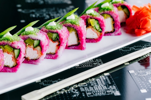 Schließen sie oben von lila sushi-rollen mit gebratenen krabbenstangen gurke und paprika