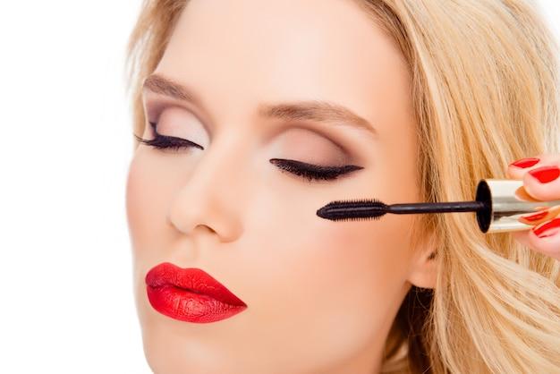 Schließen sie oben von luxusfrau mit roten lippen, die mit bürste der wimperntusche bilden
