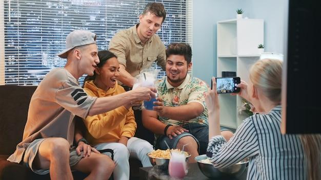 Schließen sie oben von mädchen, das foto von freunden macht, die auf sofa mit cocktails durch smartphone sitzen