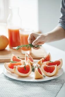 Schließen sie oben von mädchen, das platte mit geschnittener grapefruit und rosmarin verziert. fitness-ernährungskonzept. speicherplatz kopieren.