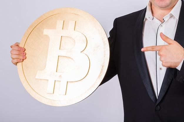 Schließen sie oben von mann, der großes bitcoin auf weißem hintergrund hält