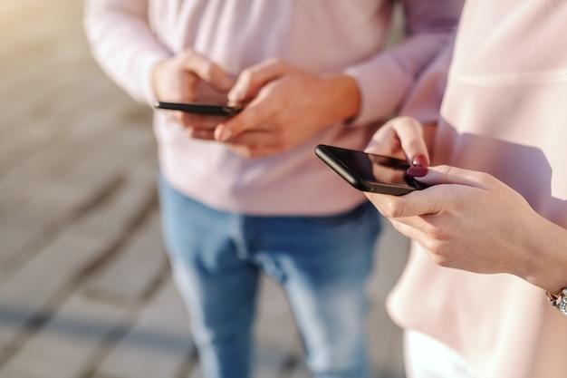 Schließen sie oben von mann und frau, die smartphones verwenden, während sie nebeneinander im freien stehen