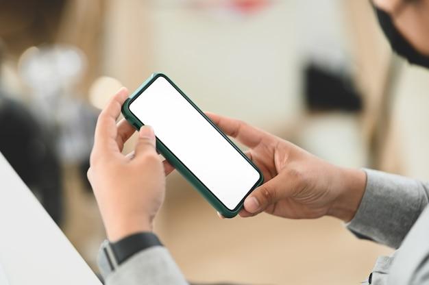 Schließen sie oben von mannhänden, die smartphone-gerät mit unscharfem bürohintergrund halten