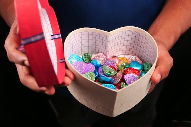 Schließen sie oben von mannhand, die herzform-geschenkbox mit süßigkeiten lokalisiert auf schwarz hält.