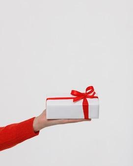 Schließen sie oben von mannhand, die weiß verpackte geschenkbox mit rotem band hält