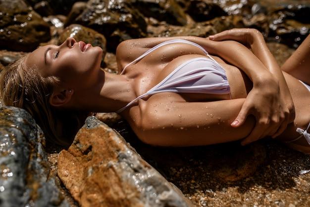 Schließen sie oben von recht jungen dünnen blondinen mit dem entspannenden strand des weißen bikinis der großen brust, der auf den großen steinen liegt. freizeit sommerkollektion mode