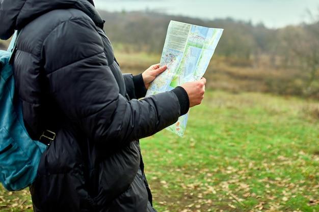Schließen sie oben von reisemann mit rucksack mit karte in der hand auf einer wand des gebirgsflusses der natur, reisekonzept, urlaub und lebensstilwanderkonzept
