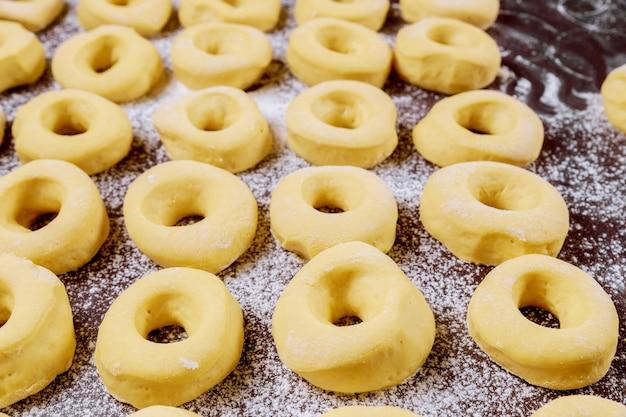 Schließen sie oben von rohen runden süßen donuts auf dem tisch mit mehl vor dem braten.