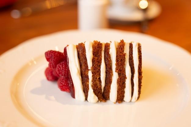 Schließen sie oben von rotem samt-stück kuchen mit himbeere auf einem teller im café
