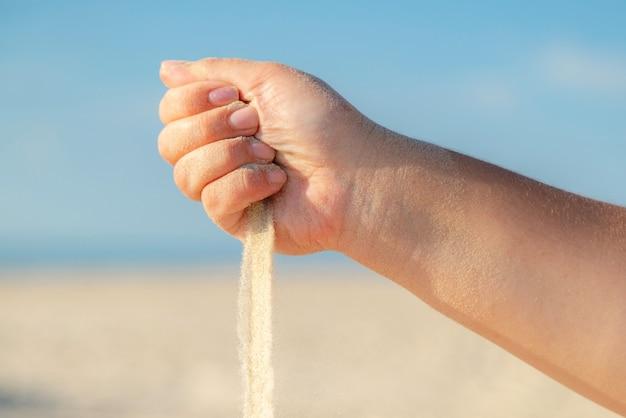 Schließen sie oben von sand, der von der hand am strand an einem sonnigen sommertag fließt.
