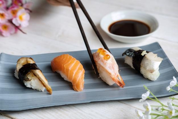 Schließen sie oben von sashimi-sushi, das mit sojasauce auf weißem holztisch gesetzt wird