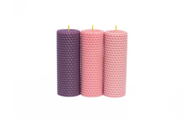 Schließen sie oben von satz von drei lila und rosa dekorativen natürlichen bienenwachskerzen mit einem honigaroma für innenraum lokalisiert auf weißem hintergrund