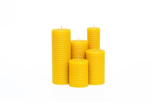 Schließen sie oben von satz von fünf gelben dekorativen natürlichen bienenwachskerzen mit einem honigaroma für innenraum lokalisiert auf weißem hintergrund