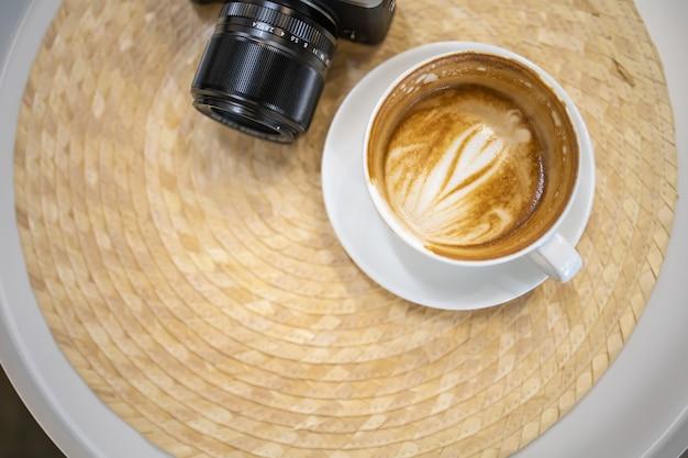 Schließen sie oben von schmutzigem weißem tasse kaffee latte mit herzformkunst auf tabelle mit kamera