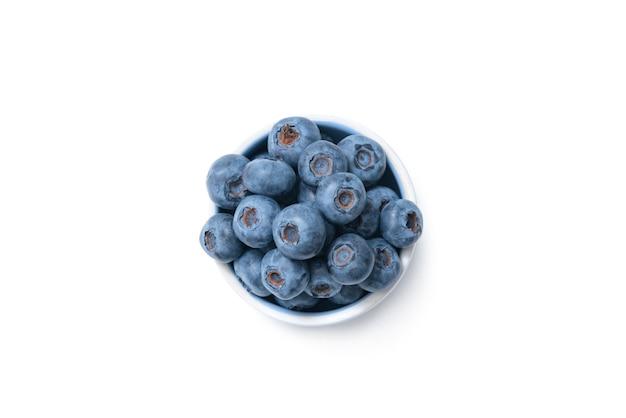 Schließen sie oben von schüssel voll von blaubeeren, die auf weißer oberfläche isoliert werden.