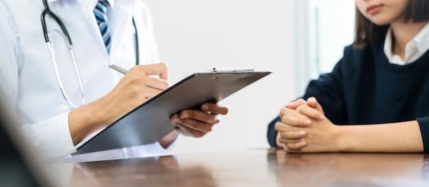 Schließen sie oben von sitzenden händen doktors und des patienten am tisch und von der unterhaltung über den zustand des patienten.