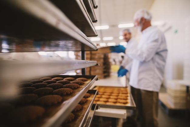 Schließen sie oben von tablett voll von frisch gebackenen keksen in der lebensmittelfabrik. verschwommenes bild von zwei männlichen angestellten in steriler kleidung im hintergrund.