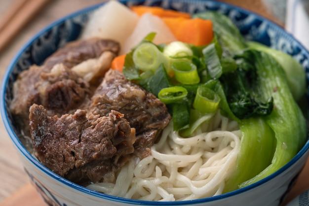 Schließen sie oben von taiwanesischem berühmtem essen mit geschnittenem geschmortem rindfleischschenkel und gemüse in einer schüssel auf holztisch