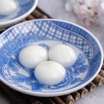 Schließen sie oben von tangyuan für wintersonnenwende festival essen auf grauem tisch hintergrund.
