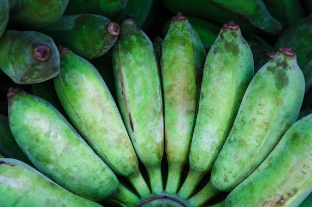 Schließen sie oben von tropischen reifen musa grünen bananen für desserts oder vegetarische mahlzeit. thailändischer obstmarkt.