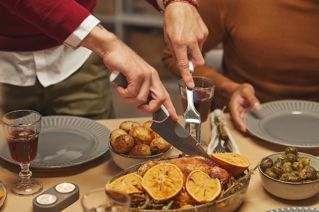 Schließen sie oben von unerkennbarem mann, der köstliches gebratenes huhn schneidet, während thanksgiving-abendessen mit freunden und familie genießt,
