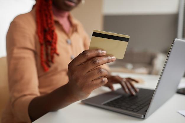 Schließen sie oben von unerkennbarer afroamerikanischer frau, die kreditkarte beim online-einkauf von zu hause laptop, kopienraum hält
