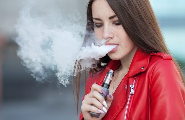 Schließen sie oben von vaping junges mädchen, das modernes e-zig-gerät in den lippen hält. quuit raucht nikotin. junge raucherin mit elektronischem zigaretten-gadget.