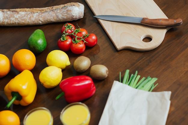 Schließen sie oben von verschiedenen bunten frischen früchten und gemüse auf dem tisch in der küche.