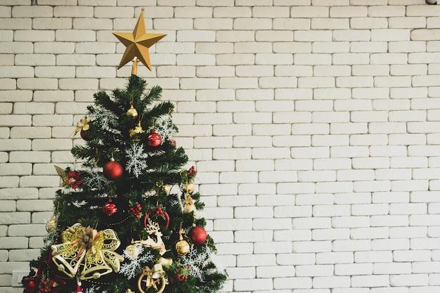 Schließen sie oben von verziertem weihnachtsbaum mit weißer backsteinmauer.