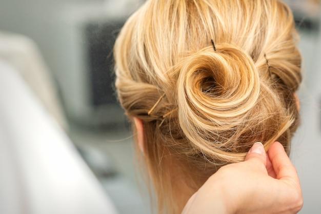 Schließen sie oben von weiblichem friseur, der blondes haar einer jungen frau in einem schönheitssalon stylt