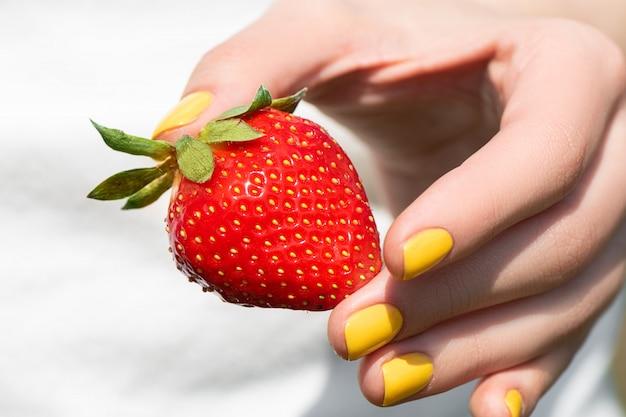 Schließen sie oben von weiblicher hand mit hübscher gelber nageldesignmaniküre, die reife erdbeere hält.