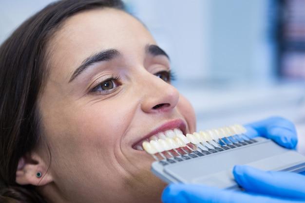 Schließen sie oben von zahnarzt, der ausrüstung hält, während frau in der klinik untersucht
